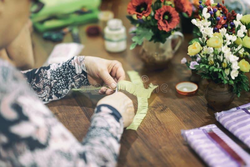 De vrouwelijke handen snijden document, makend met de hand gemaakte gift, helder kleurrijk bloemenboeket, het scrapbooking, hobby stock foto's