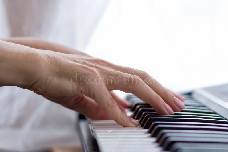 De vrouwelijke handen spelen de synthesizer royalty-vrije stock foto's