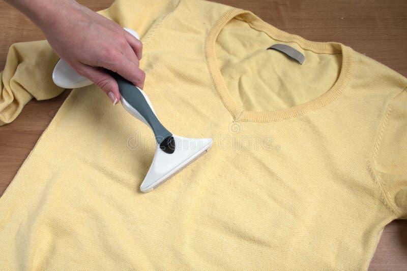 De vrouwelijke handen verwijdert dons uit gele sweater stock foto's