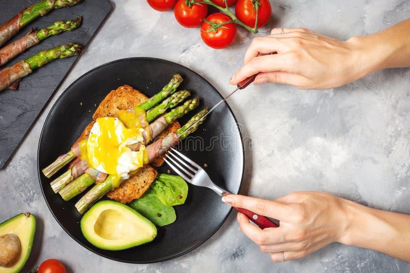 De vrouwelijke handenbesnoeiing roosterde groene die asperge met bacon wordt verpakt, stroopte Benedict ei en avocado op toosts v royalty-vrije stock afbeelding