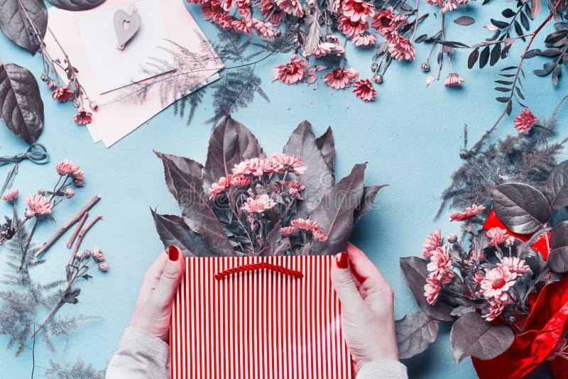 De vrouwelijke handholding bloeit regeling in rode document giftzak op bloemistbureau met vele bloemen en lege groetkaart Samenva royalty-vrije stock foto