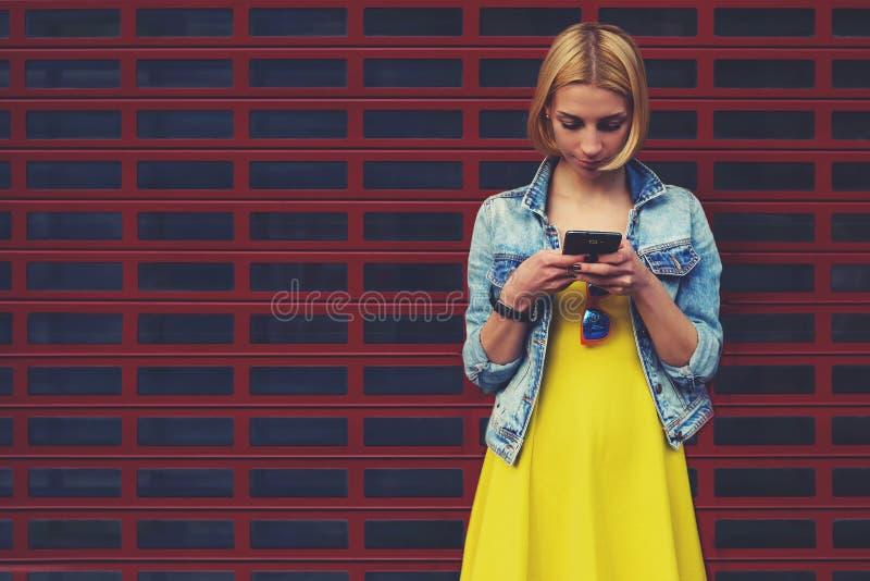De vrouwelijke hipsterstudent in de kleding die mobiele telefoon met behulp van voor verbindt met radio stock foto's