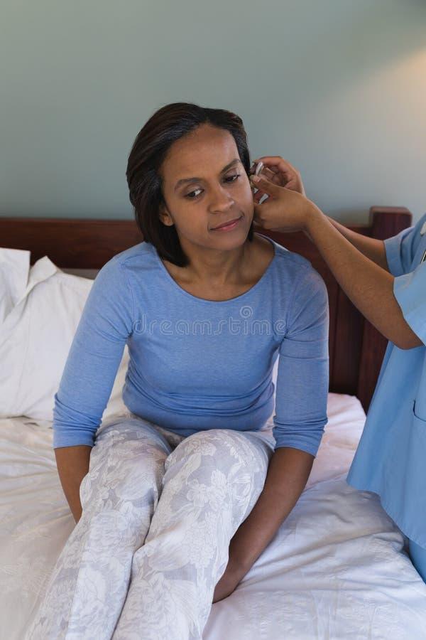 De vrouwelijke hogere vrouw van de artsenmontage met gehoorapparaat in het huis van de bedadvertentie stock foto's