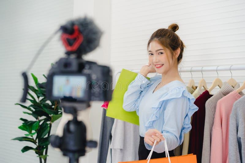 De vrouwelijke de holding van blogger online influencer het winkelen zakken en de partijen van kleren op kleren rekken voor het r royalty-vrije stock foto