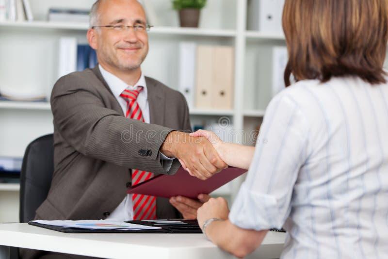 De Vrouwelijke Kandidaat van zakenmanshaking hands with stock afbeeldingen