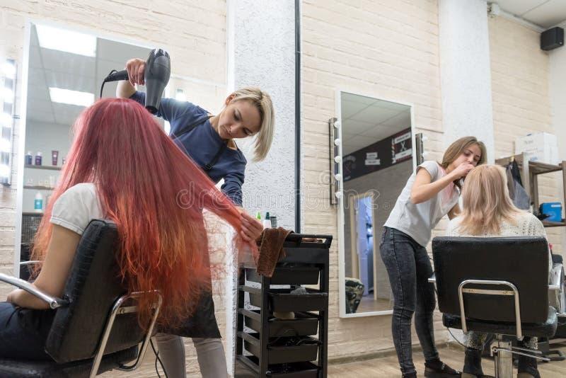 De vrouwelijke Kappers dienen vrouwencliënten in de salon van de kapper - één droogt haar haar, en andere schildert haar wenkbrau stock foto's