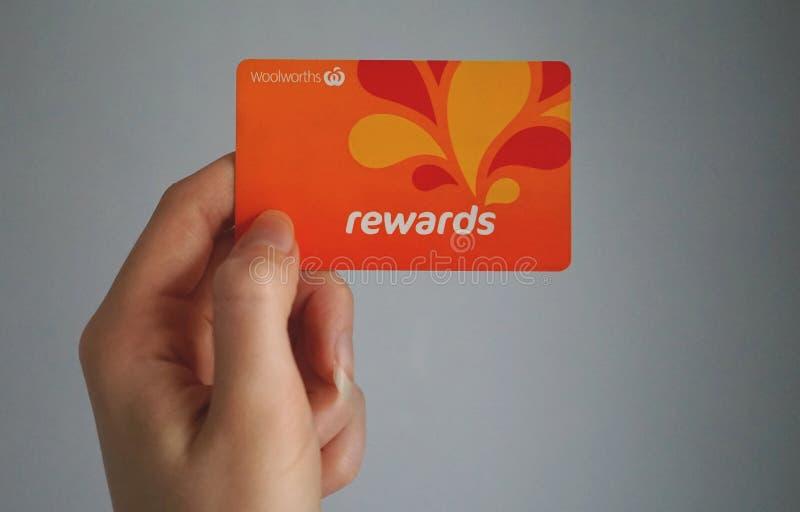 De vrouwelijke Kaukasische hand houdt een Woolworths loyaliteitskaart beloont, geeft dit loyaliteitsprogramma geld van het winkel royalty-vrije stock afbeelding