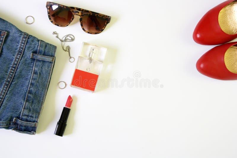 De vrouwelijke klerenvlakte legt met schoonheidsmiddelen en toebehoren op witte achtergrond stock foto's