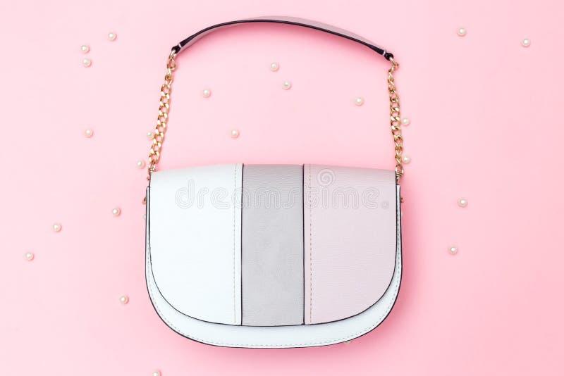 De vrouwelijke kleur van handtaspastelkleuren op roze decoratie als achtergrond en parel Vlak leg stock foto