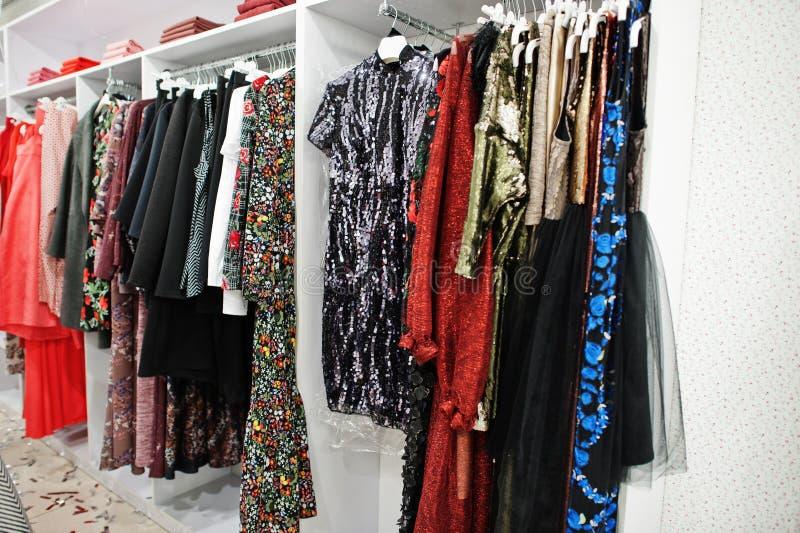 De vrouwelijke kleurrijke reeks van kledingsavondjurken van op de rekken in de gloednieuwe moderne boutique van de kledingsopslag stock foto