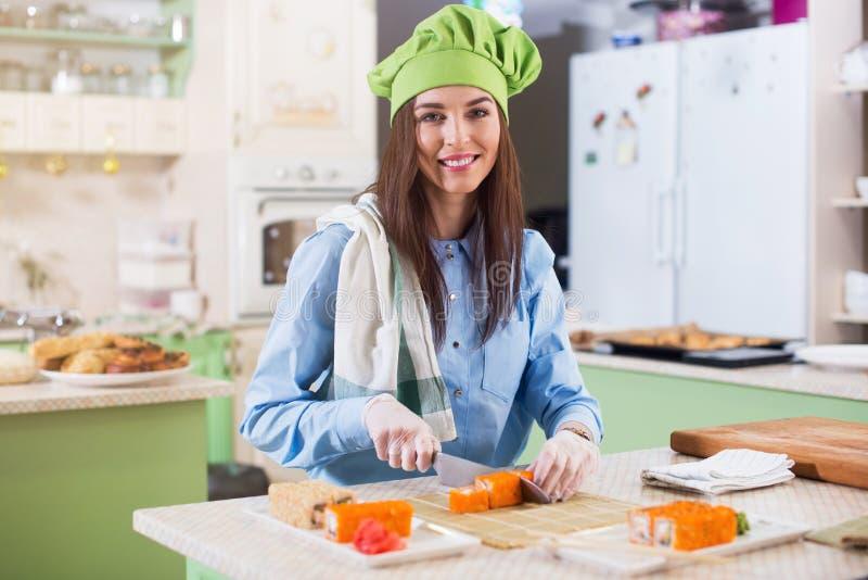 De vrouwelijke kok die Chef-koks hoed en handschoenen dragen die Japanse sushi maken rolt, het glimlachen, bekijkend camera in de royalty-vrije stock afbeelding