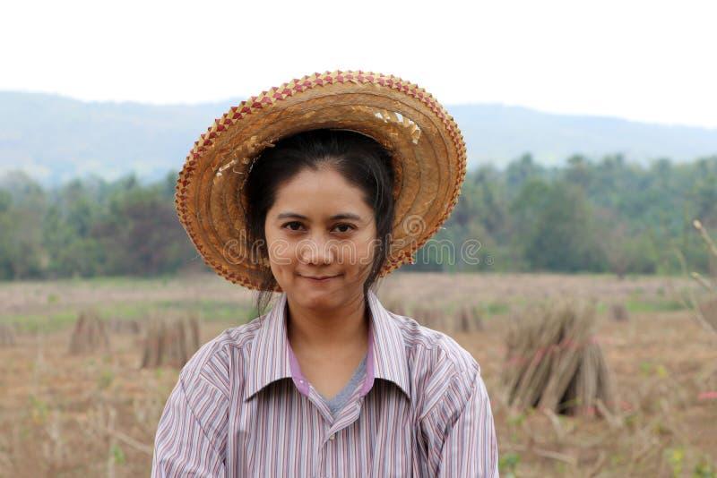 De vrouwelijke landbouwer status en concentreert uit de stapel van tapiocalidmaat in het landbouwbedrijf royalty-vrije stock fotografie