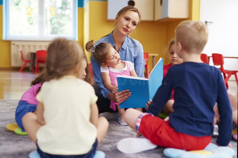 De vrouwelijke leraar en de groep kinderen lezen een boek stock afbeelding