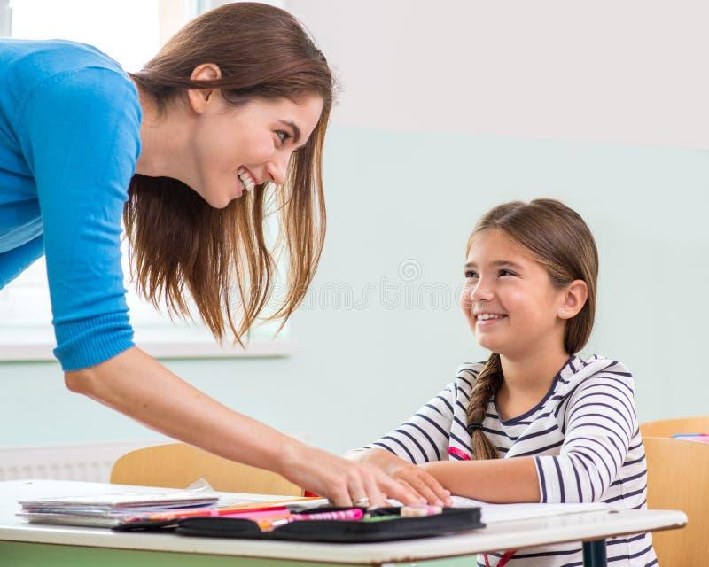 De vrouwelijke leraar toont de kinderen het boek, het lezen royalty-vrije stock afbeeldingen