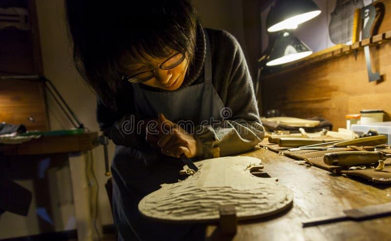 De vrouwelijke maker die van de vakmanviool aan een nieuwe viool werken stock fotografie
