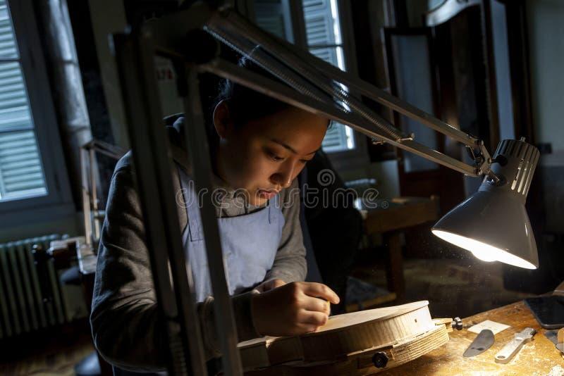 De vrouwelijke maker die van de vakmanviool aan een nieuwe viool werken stock foto's