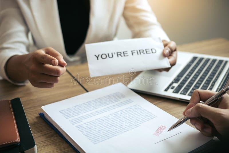 De vrouwelijke manager deelde het ontslagcertificaat aan de mannelijke werknemer uit terwijl het ondertekenen van het contract om stock foto