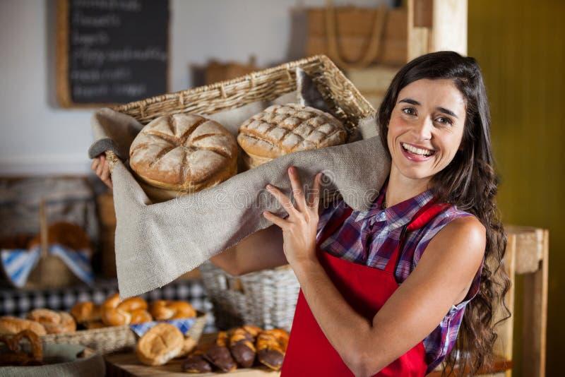 De vrouwelijke mand van de personeelsholding zoet voedsel in bakkerijsectie royalty-vrije stock afbeeldingen