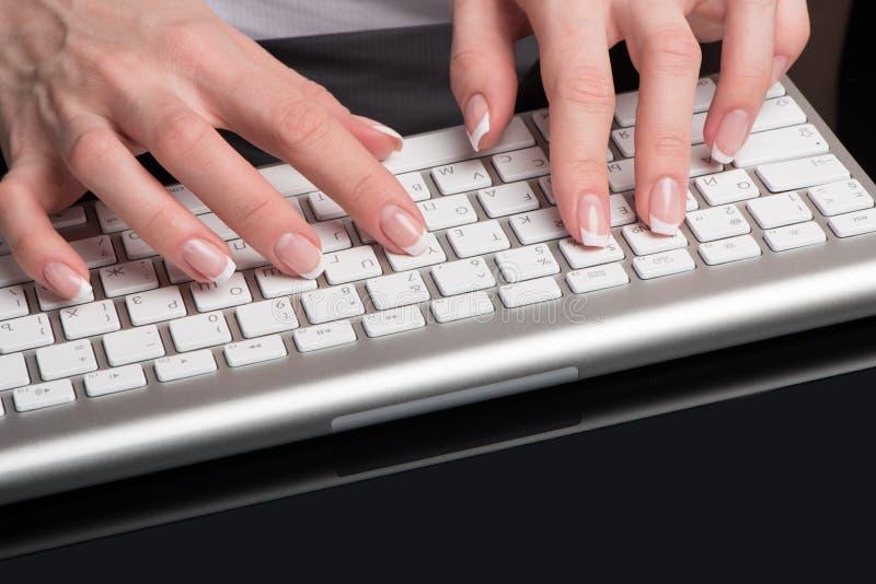 De vrouwelijke mooie handen met klassieke Franse manicure worden gevestigd over het computertoetsenbord royalty-vrije stock afbeeldingen