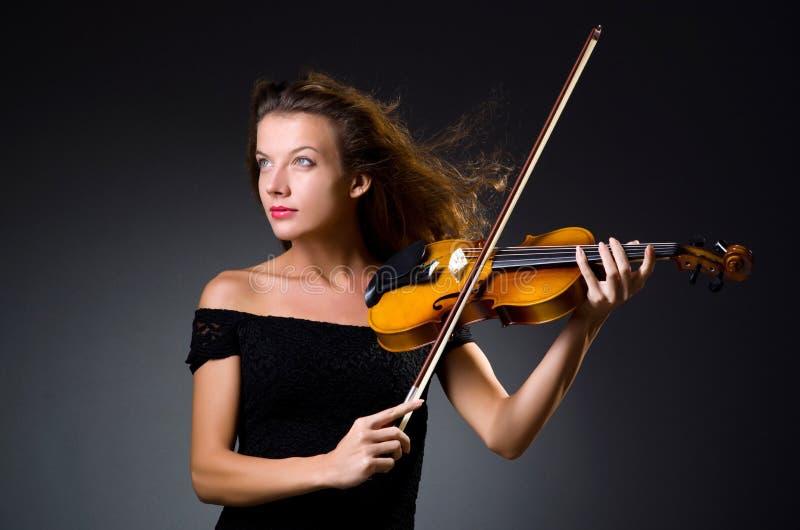 De vrouwelijke muzikale speler tegen dark stock fotografie