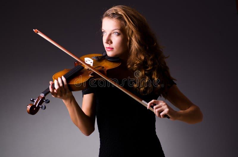 De vrouwelijke muzikale speler tegen dark stock foto's