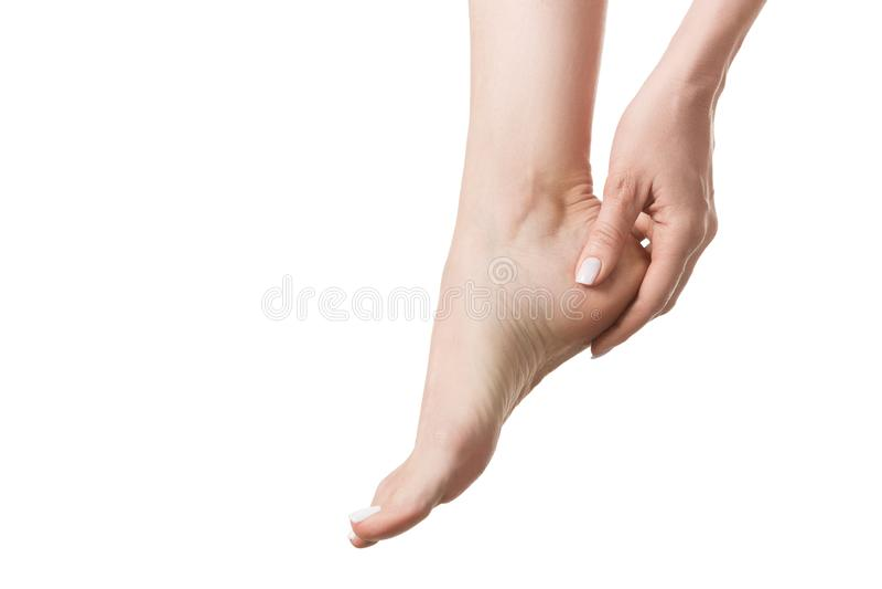 De vrouwelijke naakte die voet van strak schoeisel, vrouw wordt vermoeid raakt haar hiel door vingers Ge?soleerd op wit, sluit om royalty-vrije stock afbeelding