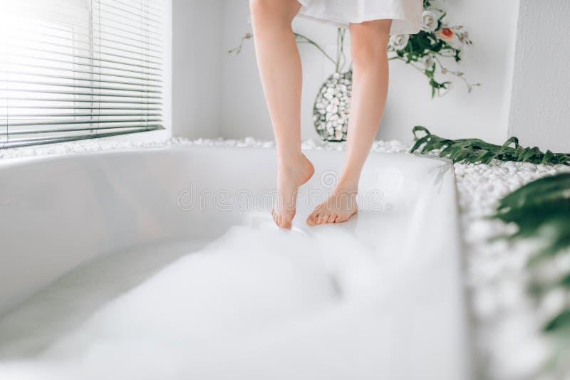 De vrouwelijke onderdompelingen van persoonsbenen in het bad met schuim royalty-vrije stock afbeelding