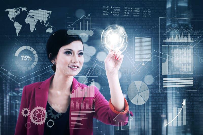 De vrouwelijke ondernemer drukt knoop op het futuristische scherm royalty-vrije stock afbeeldingen