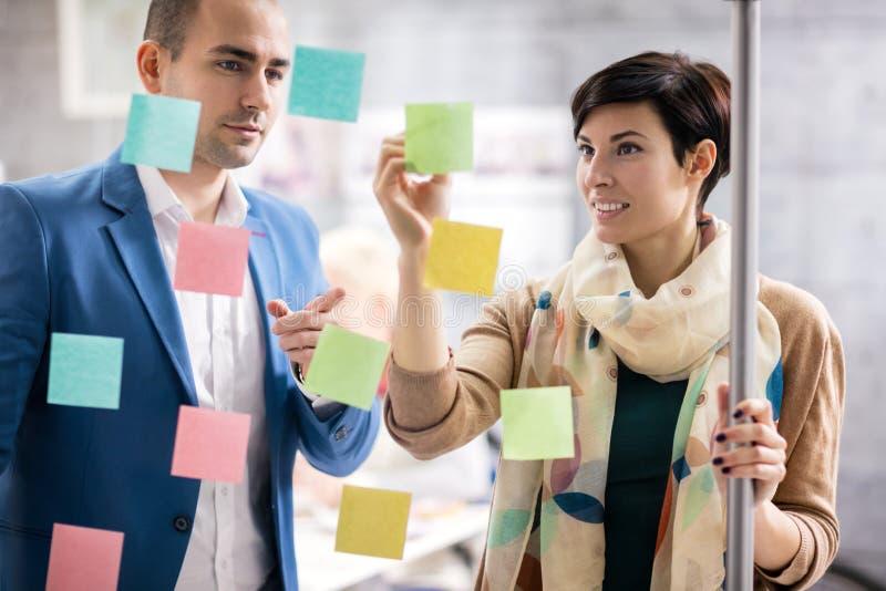 De vrouwelijke ontwerper en de medewerker maken businessplan stock foto