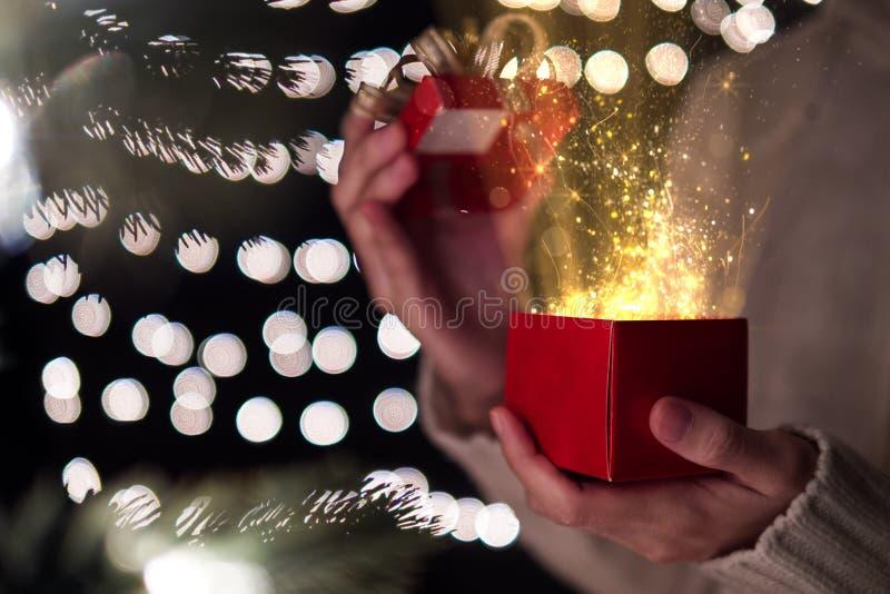 De vrouwelijke open rode doos van de Kerstmisgift met gouden straal van magisch licht op bokeh lichte achtergrond stock foto