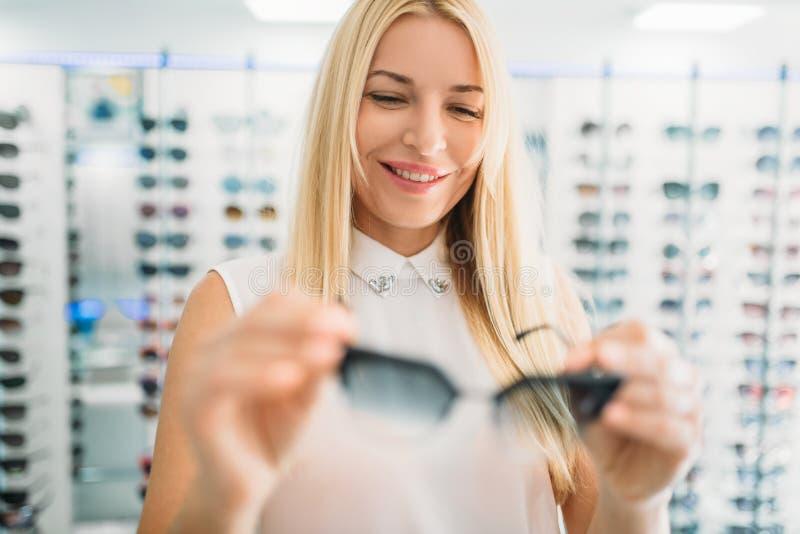De vrouwelijke opticien toont zonnebril in opticaopslag royalty-vrije stock fotografie