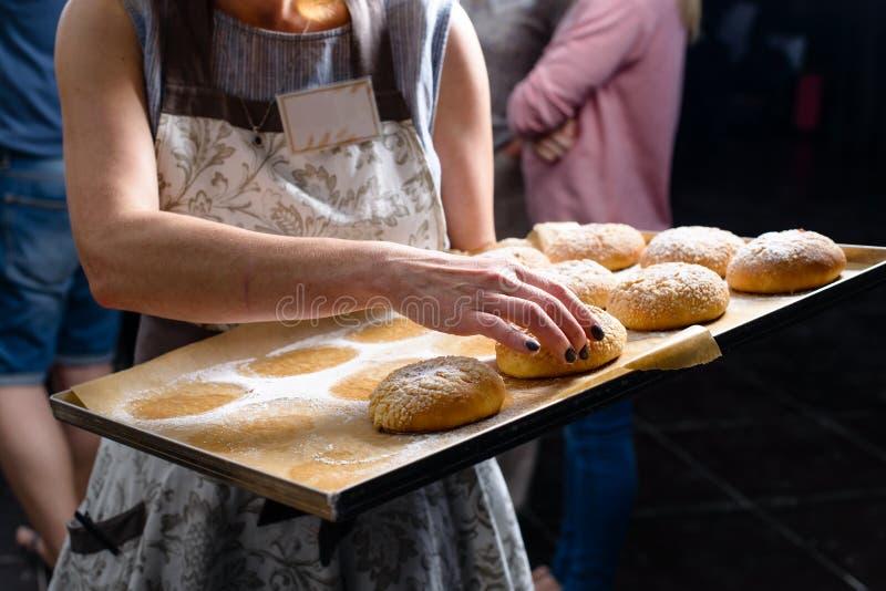 De vrouwelijke pan van de chef-kokholding met verse zoete broodjes Bakselcakes coo royalty-vrije stock foto