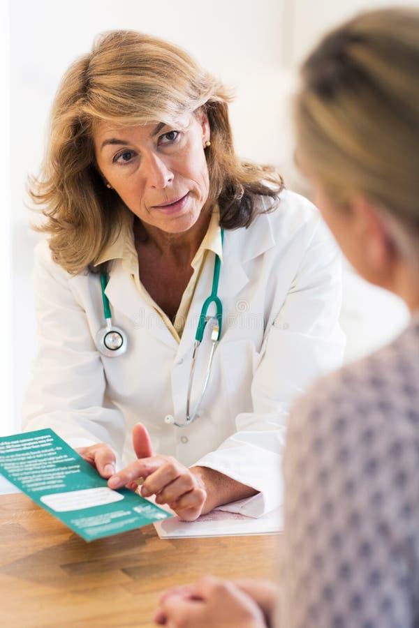 De Vrouwelijke Patiënt van artsendiscussing leaflet with royalty-vrije stock foto's