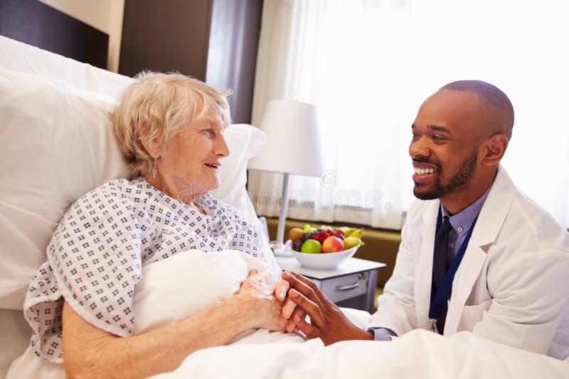 De Vrouwelijke Patiënt van artsentalking to senior in het Ziekenhuisbed stock afbeelding