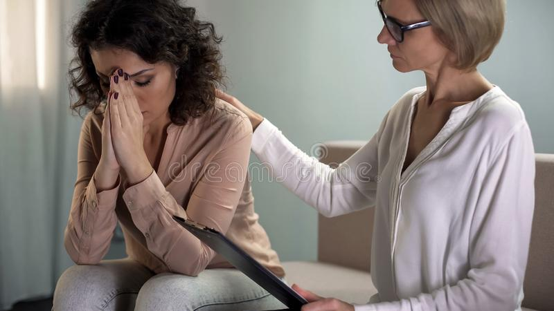 De vrouwelijke patiënt van de psycholoog troostende gedeprimeerde jonge dame, geestelijke gezondheid royalty-vrije stock afbeelding