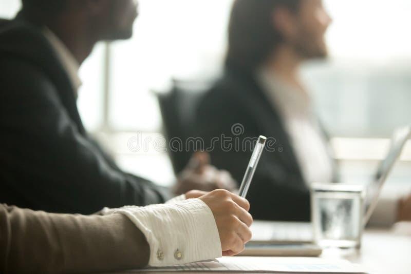 De vrouwelijke pen die van de handholding nota's maken op vergadering, close-upmening royalty-vrije stock fotografie