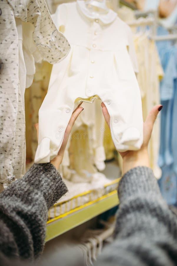 De vrouwelijke persoon kiest babykleren in de opslag royalty-vrije stock fotografie