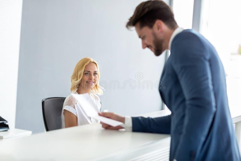 De vrouwelijke receptionnist bekijkt knappe zakenman stock foto's