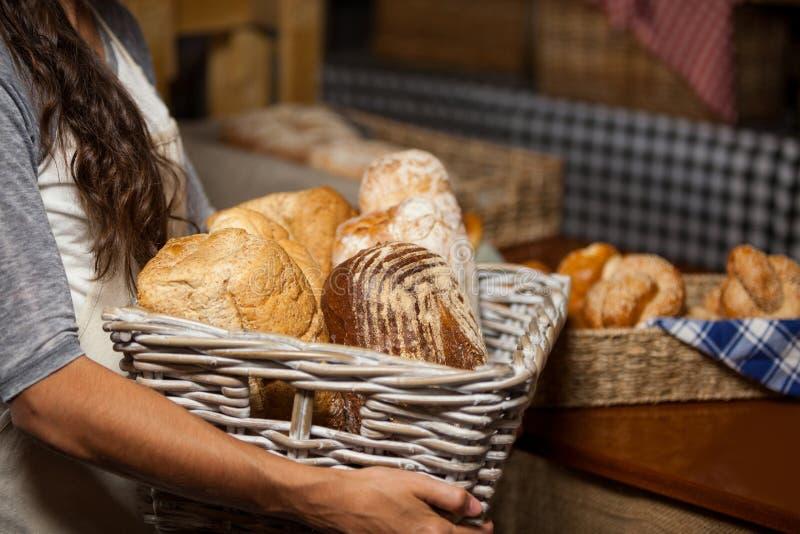 De vrouwelijke rieten mand van de personeelsholding diverse broden bij teller in bakkerijwinkel stock fotografie