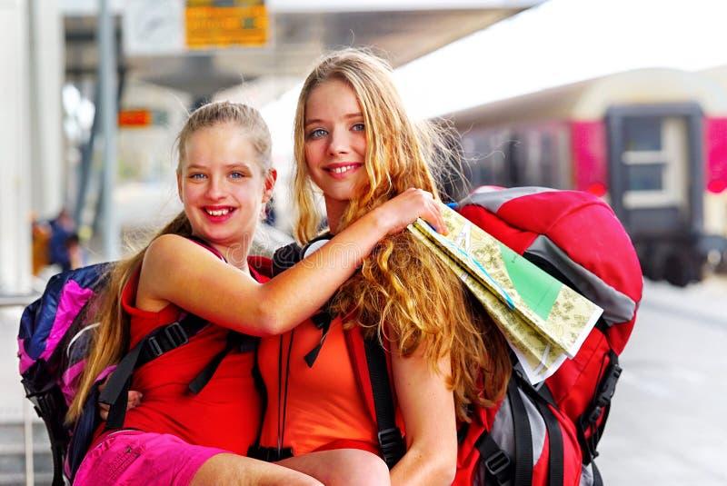 De vrouwelijke rugzak van het reizigersmeisje en toerismeuitrusting bij station stock foto's