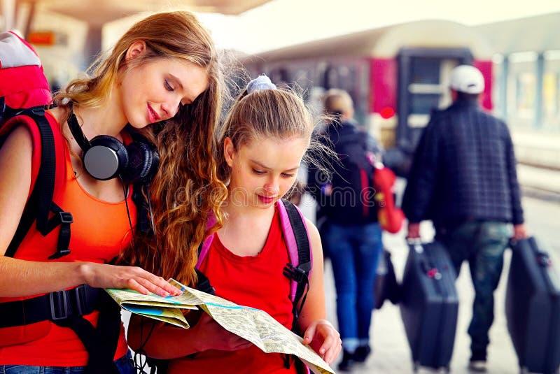 De vrouwelijke rugzak van het reizigersmeisje en toerismeuitrusting bij station stock fotografie