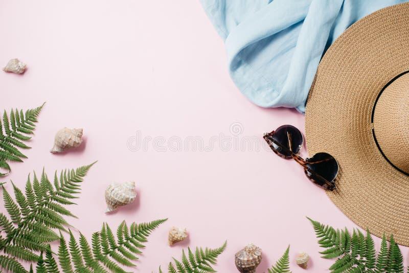 De vrouwelijke samenstelling van de de zomermanier met blouse, hoed, zonnebril, varen, zeeschelp op roze achtergrond royalty-vrije stock fotografie