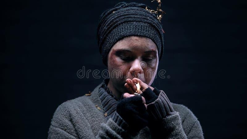 De vrouwelijke sigaret van de bedelaarverlichting, die op straat, dakloze levensstijl, probleem leven royalty-vrije stock afbeeldingen