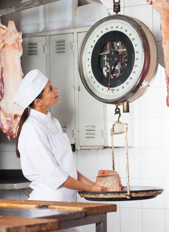 De vrouwelijke Slachterij van Slagersweighing meat in royalty-vrije stock afbeeldingen