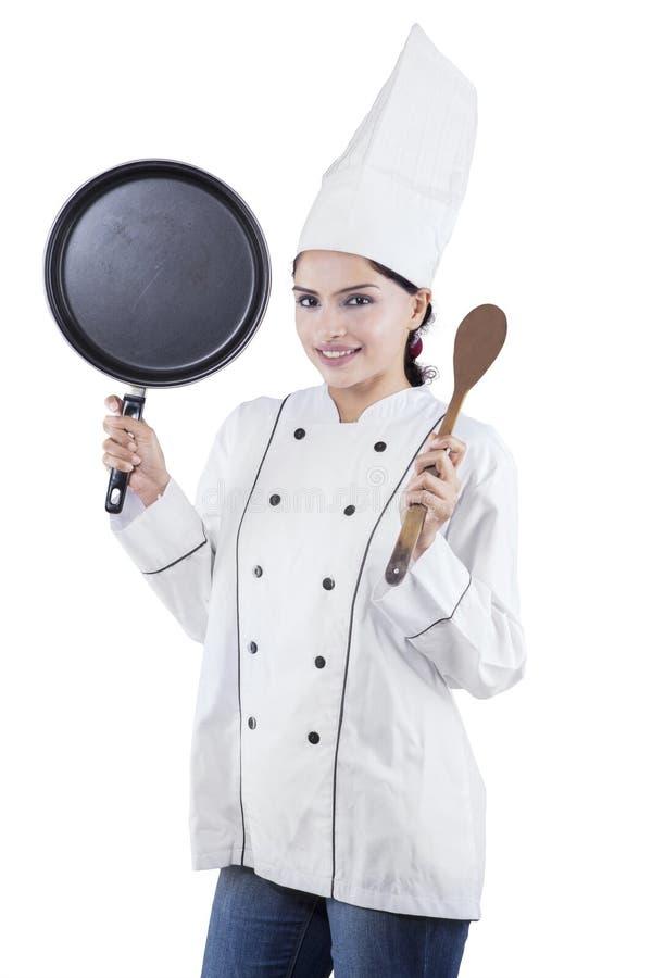 De de vrouwelijke spatel en pan van de chef-kokholding royalty-vrije stock fotografie