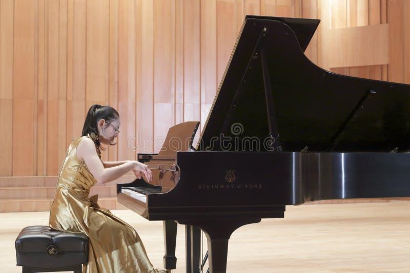 De vrouwelijke student het spelen piano stock afbeelding