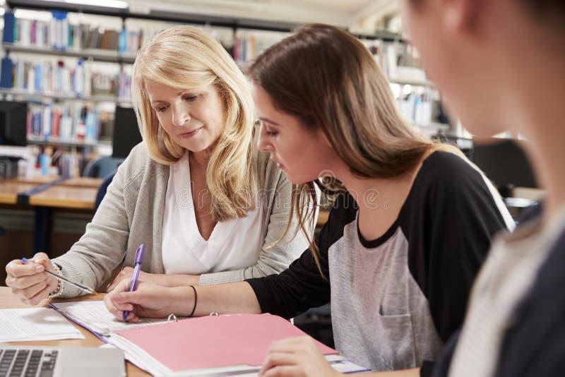 De vrouwelijke Studenten van Leraarsworking with college in Bibliotheek stock foto's