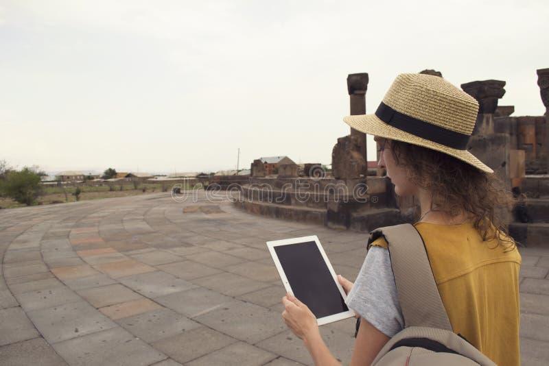 De vrouwelijke tablet van de reizigersholding tijdens het bezoeken Zvartnots Armenië Technologie en het reizen royalty-vrije stock fotografie