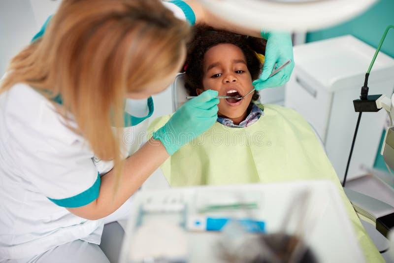De vrouwelijke tand van de tandartsreparatie aan aardig zwart jong geitje stock afbeelding