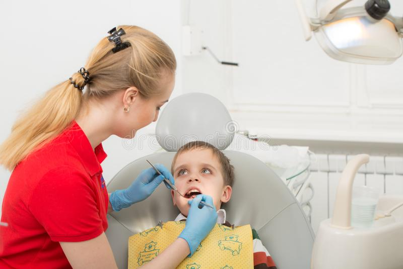 De vrouwelijke tandarts onderzoekt de tanden van het geduldige kind kindmond wijd open als tandarts` s voorzitter Close-up royalty-vrije stock foto's